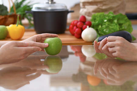 Two women discussing a new menu in the kitchen, close up. Human hands of two persons gesticulating at the table among fresh vegetables. Cooking and friendship concept. Imagens