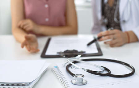 Stethoscope, medical prescription form are lying against the background of a doctor and patient discussing health exam results