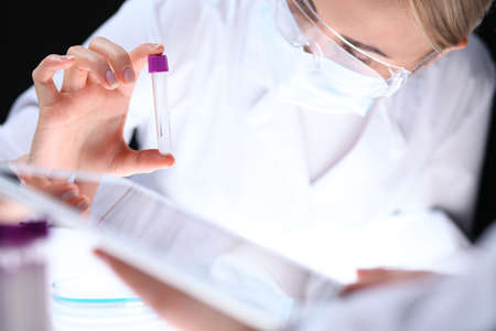 Close up of scientific research team with clear solution in laboratory Stock Photo