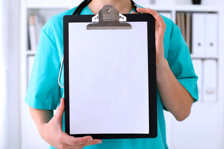 medical laboratory: Close-up of a female surgeon doctor is showing copy space - empty application form