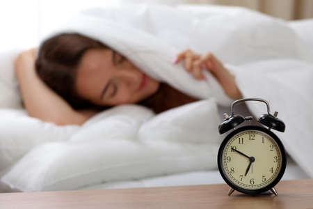 Alarm clock standing on bedside table has already rung early morning to wake up woman in bed sleeping in background. Early awakening, not getting enough sleep, oversleep, time line concept