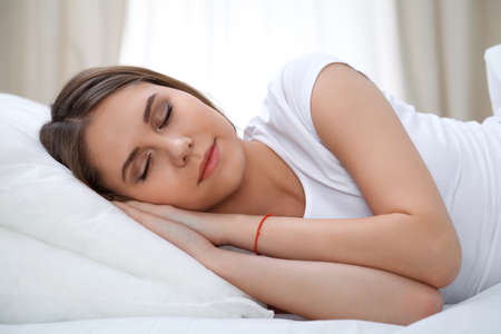 blissfully: Beautiful young and happy woman sleeping while lying in bed comfortably and blissfully smiling Stock Photo