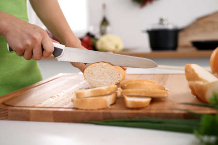Close up of womans hands cooking in the kitchen. Housewife slicing white bread. Vegetarian and healthily cooking concept.