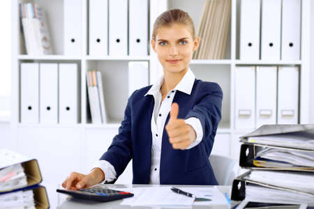 Modern business woman or confident female accountant, thumb up Stock Photo