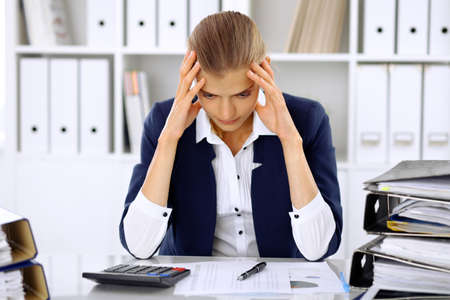 Tired business woman or female accountant with bills and paper folders in office