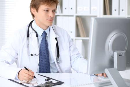 Friendly médico masculino está sentado en la mesa y trabajando en la oficina del hospital. Listo para examinar y ayudar a los pacientes. Alto nivel y concepto de servicio médico de calidad.