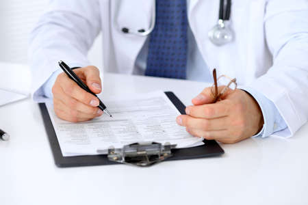 Close up of male doctor is sitting at the table and filling up medical history form