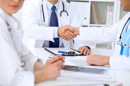 handclasp: Two doctors shaking hands to each other sitting at the table in hospital office.