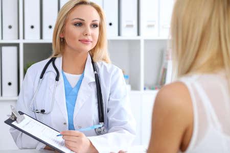 Doctor y paciente discutiendo algo mientras médico apuntando a formulario de historia médica en portapapeles