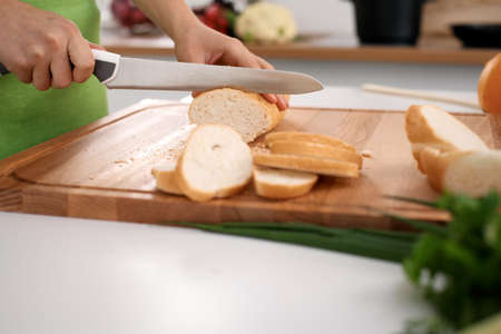 Close up of womans hands cooking in the kitchen. Housewife slicing white bread. Vegetarian and healthily cooking concept