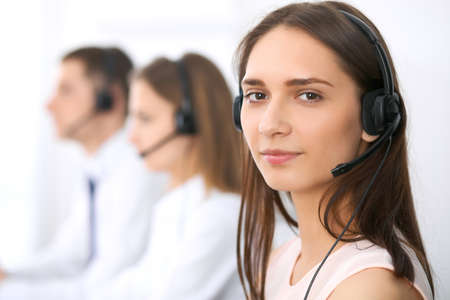 customer support: Call center operators. Focus at young beautiful business woman in headset