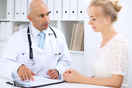 Confident bald doctor man consults his female patient