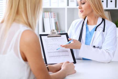 Doctor y paciente que discuten algo mientras que phisician que señala en forma de la historia médica en el tablero. Medicina y concepto de cuidado de la salud Foto de archivo
