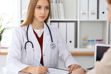 Doctor and  patient  sitting at the desk. Medicine and health care concept Stock Photo