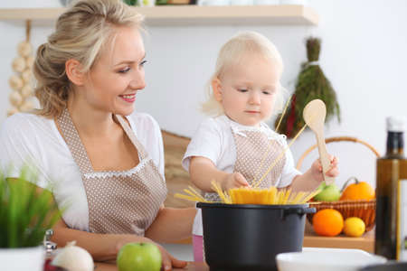 Happy family in the kitchen. Mother and child daughter cooking pasta 스톡 콘텐츠
