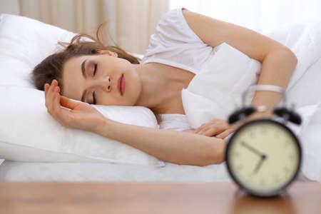 Krásná mladá žena spí ležet v posteli a relaxaci ráno. Začátek slunečného dne je čas, kdy můžete za víkend chodit na práci nebo spát