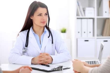 Brunette vrouwelijke dokter praten met patiënt in het ziekenhuis