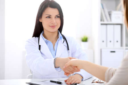 hospital patient: Brunette female doctor shaking hands with patient during a conversation with her