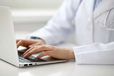 Female doctor typing on laptop, close up.