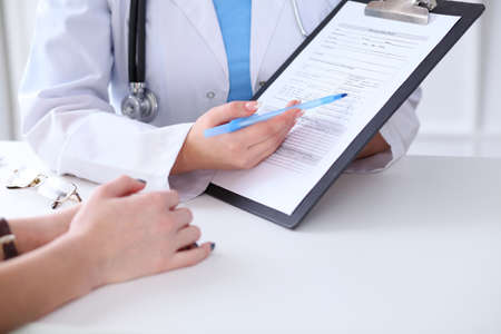 phisician: Close up of a doctor and  patient hands while phisician pointing into medical history form at clipboard. Medicine and health care concept