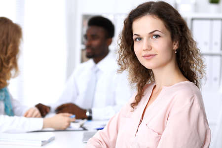 Beautiful business woman at meeting in white colored  office background Stock Photo