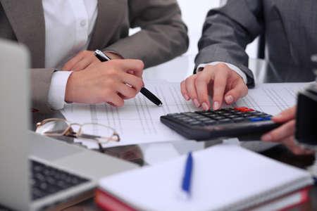 Due ragionieri femminili che contano sul reddito del calcolatore per il completamento delle mani del modulo di completamento delle tasse. Ispettore di Internal Revenue Service che controlla documento finanziario. Budget di pianificazione, concetto di audit Archivio Fotografico - 79642347