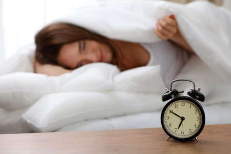 Alarm clock standing on bedside table has already rung early morning to wake up woman in bed sleeping in background