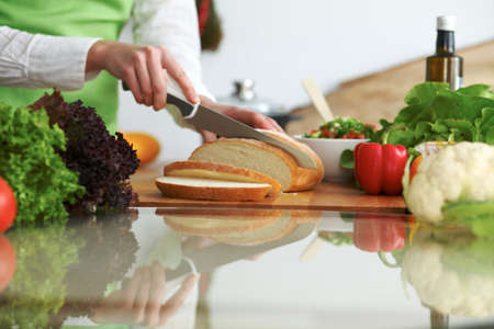 Closeup of human hands cooking in kitchen on the glass table with reflection. Housewife slicing bread