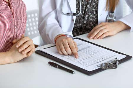Médico y paciente sentado en el escritorio. Médico apuntando a registros de historia médica y explicando algo a la mujer joven. Concepto de medicina y salud. Foto de archivo - 79662011