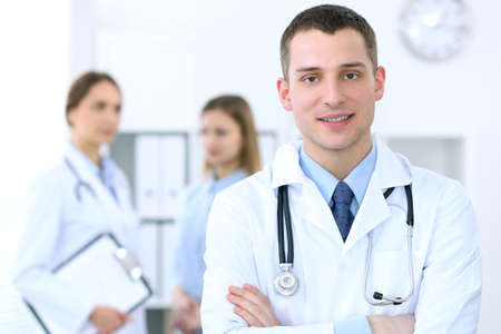 Friendly male doctor  on the background with patient  and physician Foto de archivo