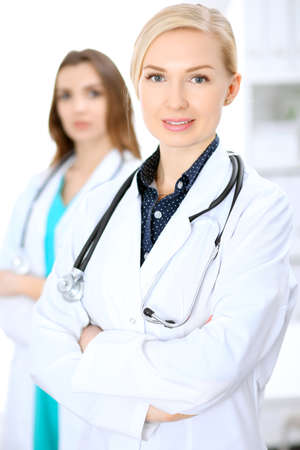 Female doctor smiling on the background with patient. Stock Photo