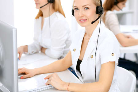 Call center. Focus on beautiful woman in headset