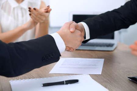 Close-up van zakenmensen handen schudden bij vergadering of onderhandeling in het kantoor. Partners zijn tevreden over het ondertekenen van contract Stockfoto
