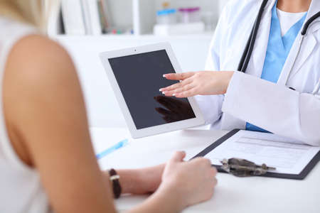 phisician: Close up of a doctor and  patient hands while phisician pointing into tablet computer monitor