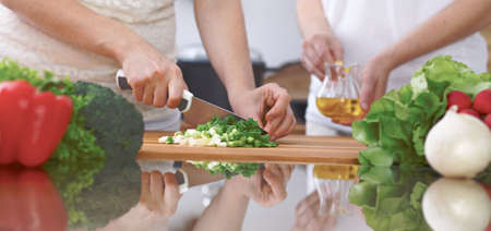 Close-up of four human hands are cooking in a kitchen. Friends having fun while preparing fresh salad. Chef cook represent culinary masterclass. Vegetarian, healthy meal and friendship concept