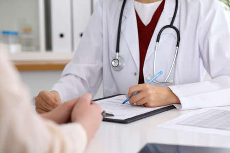 oncologist: Close up of a female doctor filling up  an application form while consulting patient. Medicine and health care concept Stock Photo