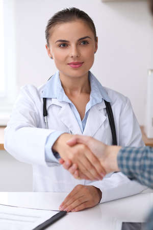 Doctor woman smiling while shaking hands with her male patient. Medicine and trust concept