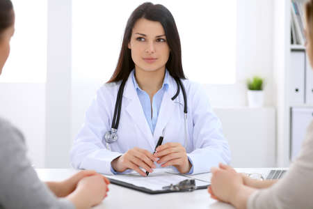 hospital patient: Brunette female doctor talking to patient in the hospital