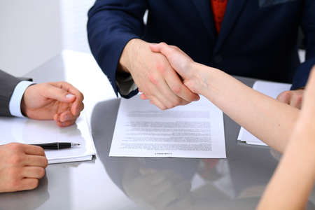 signed: Businessman and business woman shaking hands to each other above signed contract