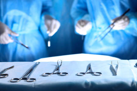 Surgical tools lying on the table while group of surgeons at background operating patient. Steel medical instruments ready to be used.