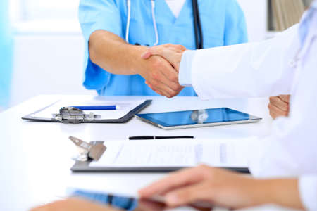 joining: Doctors shaking hands to each other finishing up medical meeting.