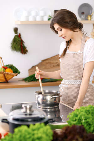 Young woman in a dotted biege apron cooking soup in the kitchen