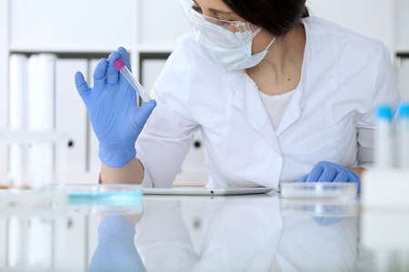 Close up of scientific research hands with clear solution in laboratory.