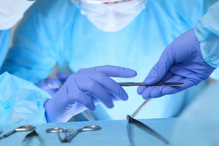 outerwear: Close up of medical team performing operation. Group of surgeons at work in operating theater. Stock Photo