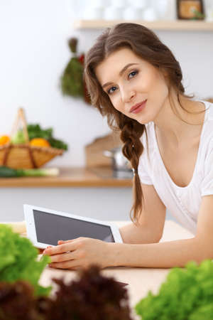 Young  woman looking for a new recipe for  cooking in a kitchen. Housewife is making online shopping by tablet computer and credit card