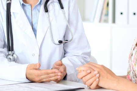 Close up of a doctor and  patient sitting at the table, just hands Stock Photo