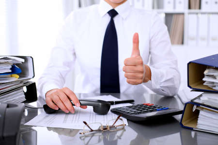 Close up of business woman showing ok sign while making report, calculating or checking balance.
