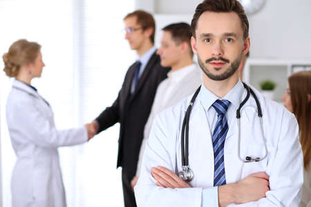 Friendly male doctor on the background doctor and patient shaking hands. Medical trust and ethics concept Stock Photo