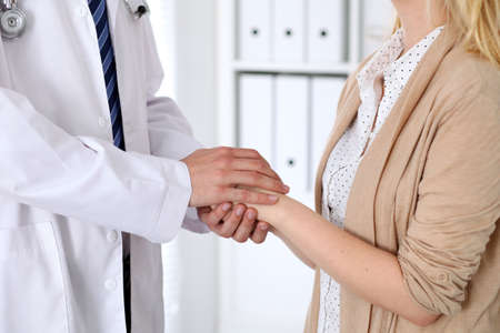 oncologist: Hand of doctor  reassuring her female patient. Medical ethics and trust concept