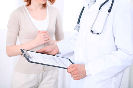 oncologist: Close up of a male doctor holding an application form while consulting patient